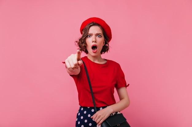 Ongelukkige vrouw in elegante rode baret wijzende vinger. bezorgd frans vrouwelijk geïsoleerd model.