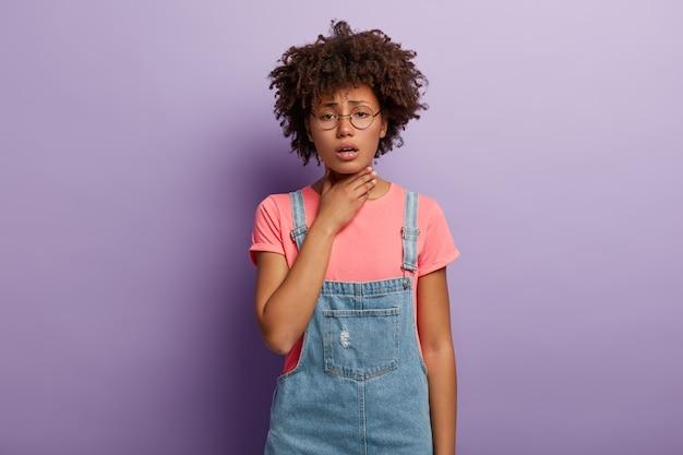 Ongelukkige vrouw met donkere huid houdt ontstoken keel vast, voelt pijn tijdens het slikken, hoest, gekleed in stijlvolle kleding, bril geïsoleerd over paarse muur. slechte symptomen. problemen met de gezondheid