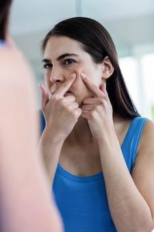 Ongelukkige vrouw met huidirritatie die haar gezicht thuis schoonmaakt
