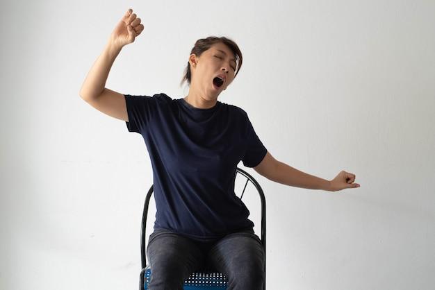 Ongelukkige vrouw zit tegen de muur, steek haar hand in de lucht en strek zich uit, lui en stress
