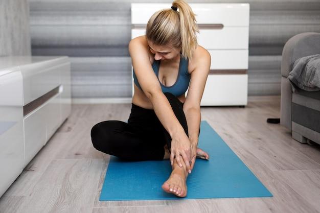 Ongelukkige vrouw zittend op de yogamat met enkelblessure, pijn voelen