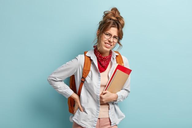 Ongelukkige vrouwelijke leerling of student draagt zware rugzak met boeken, lijdt aan rugpijn, houdt blocnote vast, raakt taille, geïsoleerd over blauwe muur. gefrustreerde tiener heeft gezondheidsproblemen