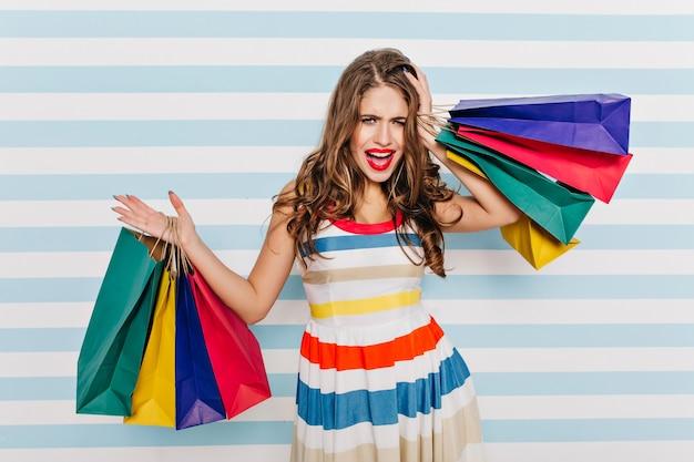 Ongelukkige vrouwelijke shopaholic vergat iets. indoor portret van glamoureuze vrouw met upleased gezichtsuitdrukking poseren met papieren zakken.