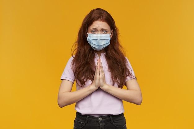 Ongelukkige, wanhopige jonge vrouw die een medisch beschermend masker draagt, houdt de handen in gebedspositie over de gele muur