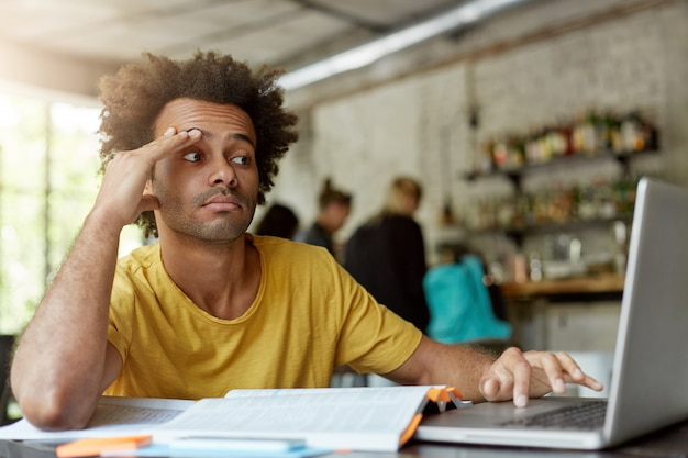Ongelukkige zwarte student in casual kleding met behulp van wi-fi op laptopcomputer, op zoek naar informatie op internet tijdens het werken aan onderzoeksproject, uitgeput kijken