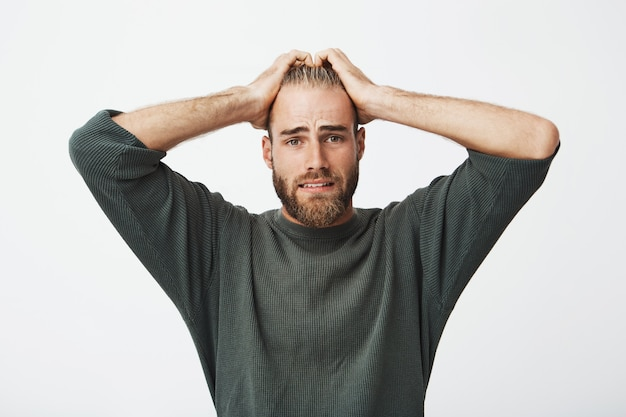 Ongelukkige zweedse jonge man met baard hand in hand op het hoofd met angstige uitdrukking