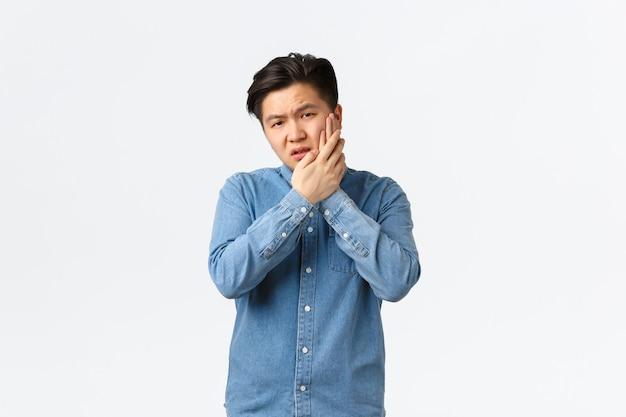 Ongemakkelijke en gehinderde aziatische man die klaagt over pijnlijk gevoel, wang aanraken, kiespijn hebben, stomatologiekliniek nodig hebben, afspraak hebben, wachten op pijnstillers, staande witte achtergrond