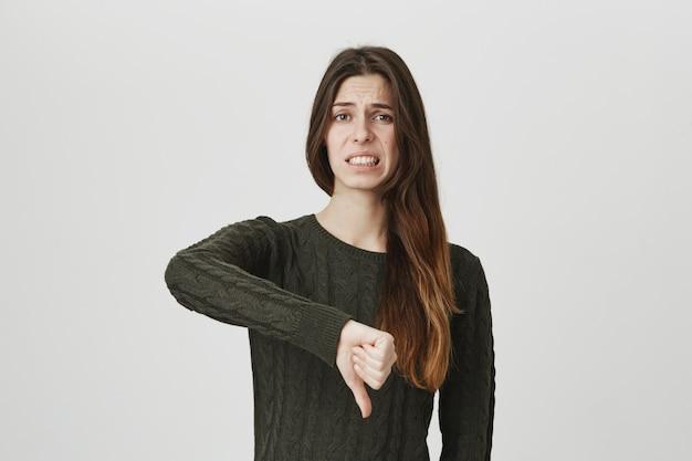 Ongemakkelijke overstuur vrouw toont duimen naar beneden, drukt afkeer en teleurstelling uit