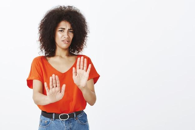 Ongemakkelijke vrouw met afro kapsel poseren in de studio