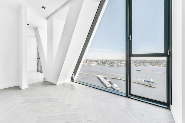 Ongemeubileerde lege ruimte met parketvloer en panoramisch muurvenster met stadsrivier in zonlicht