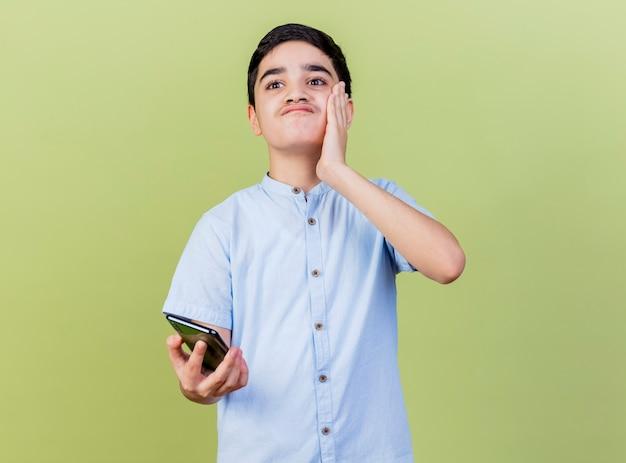 Ongenoegen jonge jongen die mobiele telefoon houdt die hand op gezicht houdt die kant bekijkt die op olijfgroene muur wordt geïsoleerd