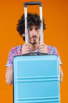Ongenoegen jonge knappe gekrulde reiziger man met koffer naar rechts op geïsoleerde oranje muur kijken