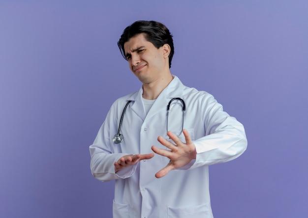 Ongenoegen jonge mannelijke arts die medische mantel en stethoscoop draagt die doet geen geïsoleerd gebaar kijkt