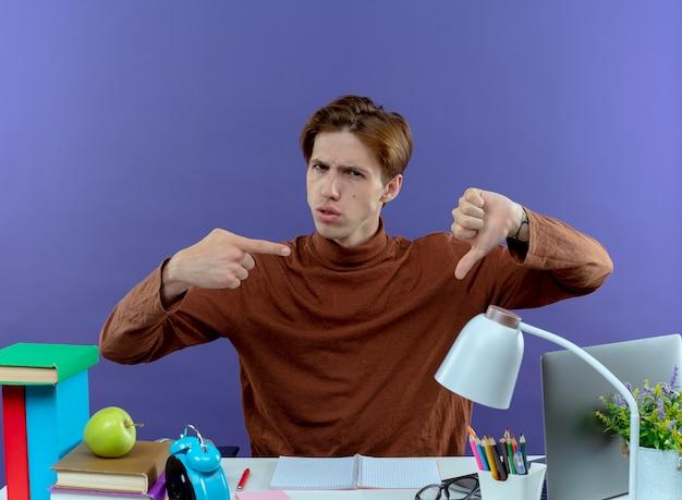 Ongenoegen jonge student jongen zittend aan een bureau met schoolgereedschap zijn duim naar beneden en wijst naar de duim op paars
