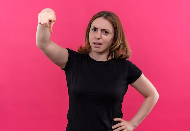 Ongenoegen jonge toevallige vrouw die met hand op taille op geïsoleerde roze muur richt
