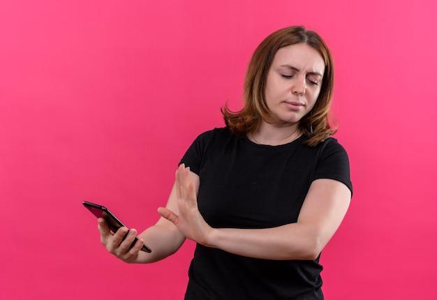 Ongenoegen jonge toevallige vrouw die mobiele telefoon houdt en nee op geïsoleerde roze muur gebaart