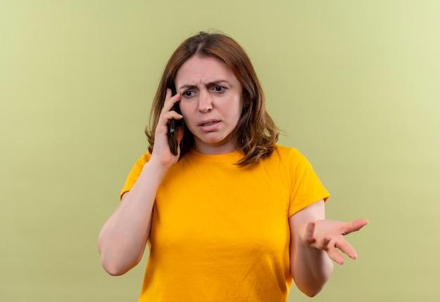 Ongenoegen jonge toevallige vrouw die op telefoon spreekt en lege hand op geïsoleerde groene muur toont