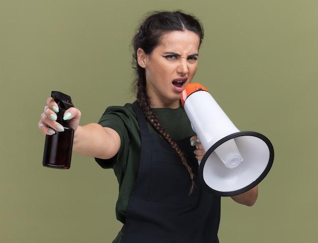 Ongenoegen jonge vrouwelijke kapper in uniform spreekt op luidspreker met spuitfles op camera geïsoleerd op olijfgroene muur
