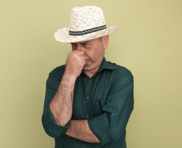 Ongenoegen kijkend naar zijman van middelbare leeftijd met een groen t-shirt en een hoed greep neus geïsoleerd op olijfgroene muur