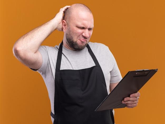 Ongenoegen slavische mannelijke kapper van middelbare leeftijd in uniform houden en kijken naar klembord geïsoleerd op oranje muur