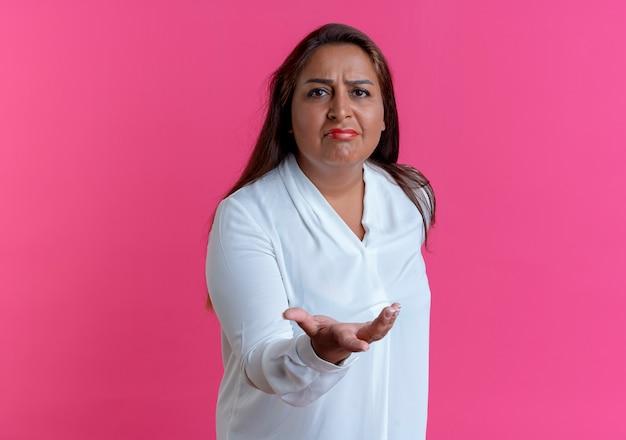 Ongenoegen toevallige kaukasische vrouw die van middelbare leeftijd hand uitstak die op roze muur wordt geïsoleerd