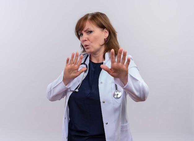 Ongenoegen vrouw arts van middelbare leeftijd die medische mantel en stethoscoop draagt ?? die stopgebaar op geïsoleerde witte achtergrond met exemplaarruimte doet