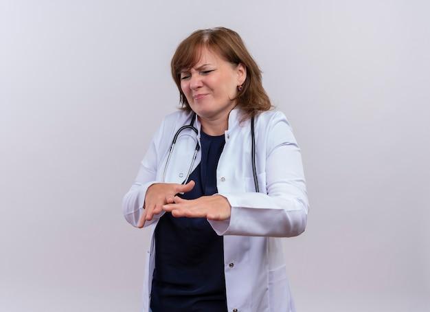 Ongenoegen vrouw arts van middelbare leeftijd die medische mantel en stethoscoop opheffende handen op geïsoleerde witte achtergrond met exemplaarruimte draagt