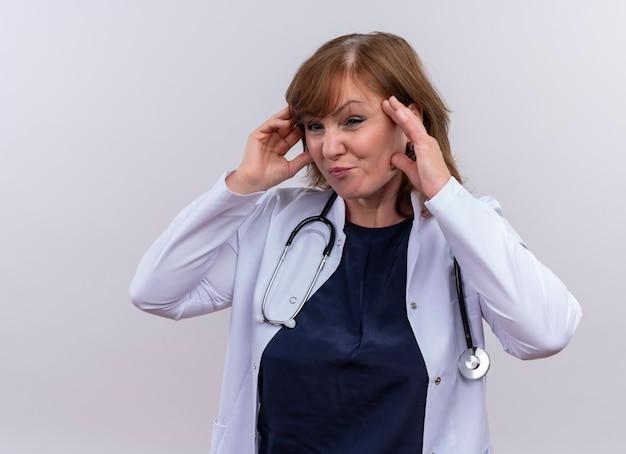 Ongenoegen vrouw van middelbare leeftijd arts die medische mantel en stethoscoop draagt ?? die handen op tempels op geïsoleerde witte achtergrond met exemplaarruimte zetten