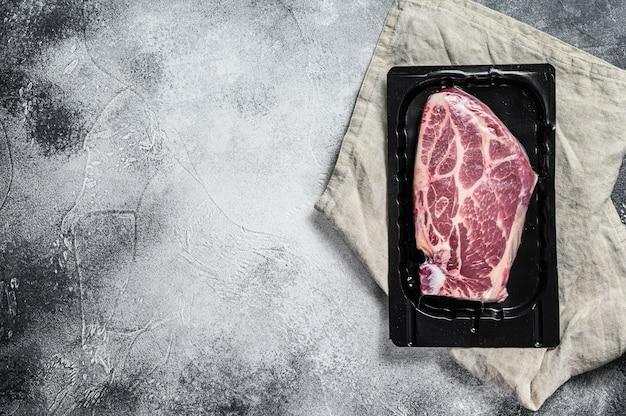 Ongeopende vacuümverpakking van varkensvlees steak geïsoleerd op zwarte achtergrond, zonder label. grijze achtergrond. bovenaanzicht. ruimte voor tekst