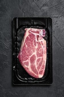 Ongeopende vacuümverpakking van varkensvlees steak geïsoleerd op zwarte muur, zonder label. zwarte muur. bovenaanzicht. ruimte voor tekst
