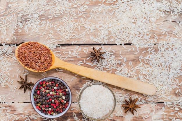 Ongepelde rijst in houten lepel met peperbollen en steranijsplant op de rustieke houten achtergrond