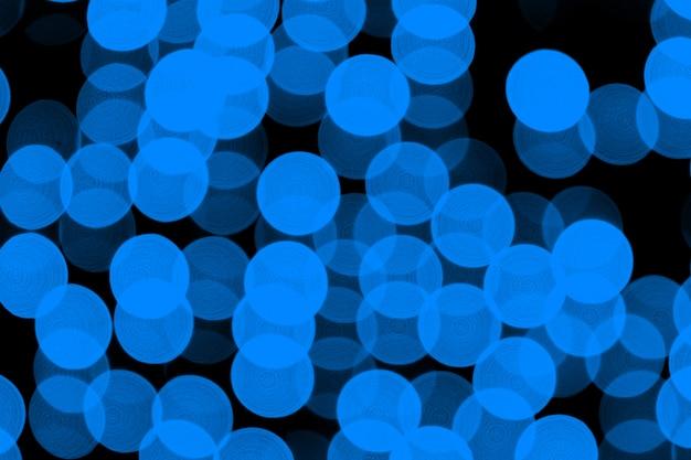 Ongericht abstracte donkerblauwe bokeh op zwarte achtergrond. onscherp en wazig veel rond licht