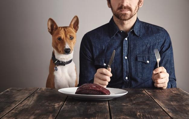 Ongericht jonge bebaarde man in werkjeans shirt en zijn mooie afrikaanse hond zitten voor witte plaat met grote rauwe walvis steak vlees in focus op grote antieke geborsteld houten tafel. wachten op het avondeten.