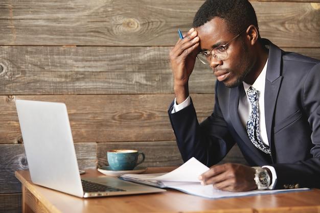 Ongerust gemaakte afrikaanse zakenman die in officieel kostuum informatie in laptop controleert