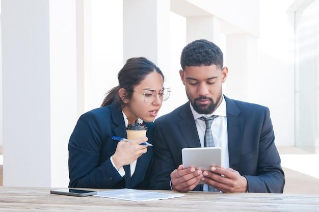 Ongerust gemaakte bedrijfsmensen die tablet gebruiken en bij bureau werken