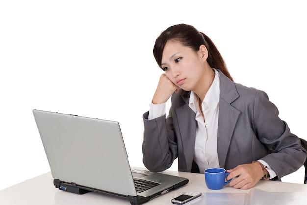 Ongerust gemaakte bedrijfsvrouw die met laptop aan bureau tegen witte achtergrond werkt.