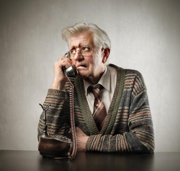 Ongerust gemaakte bejaarde die op een klassieke telefoon spreekt