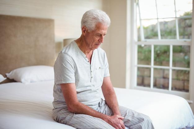 Ongerust gemaakte hogere mens die neer terwijl het zitten op bed kijkt