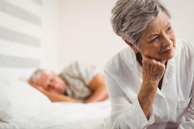 Ongerust gemaakte hogere vrouwenzitting op bed in slaapkamer