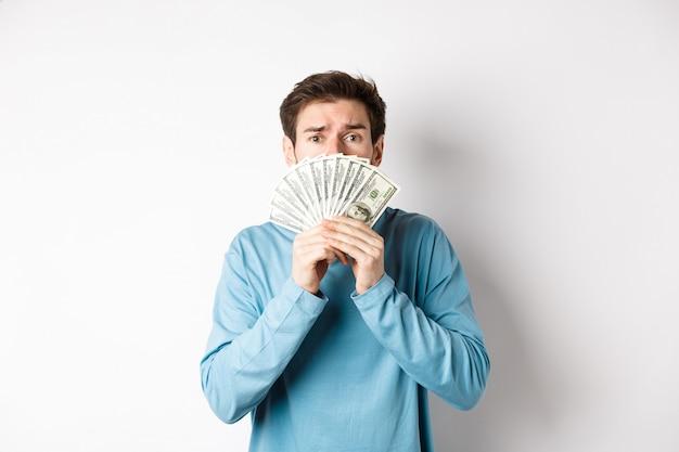 Ongerust gemaakte jonge man die met smekend gezicht kijkt, geld toont, die zich in blauw sweatshirt over witte achtergrond bevindt.