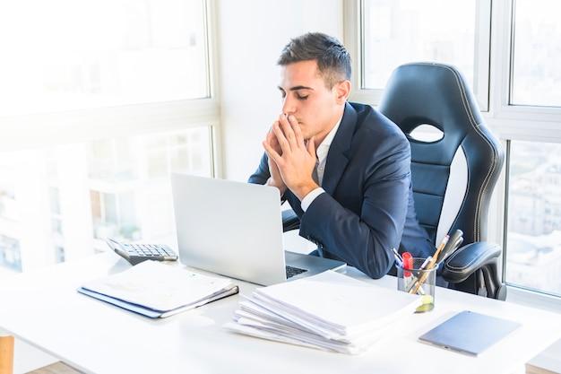 Ongerust gemaakte jonge zakenman die laptop in het bureau bekijkt
