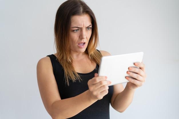 Ongerust gemaakte vrouw die het tabletscherm bekijkt