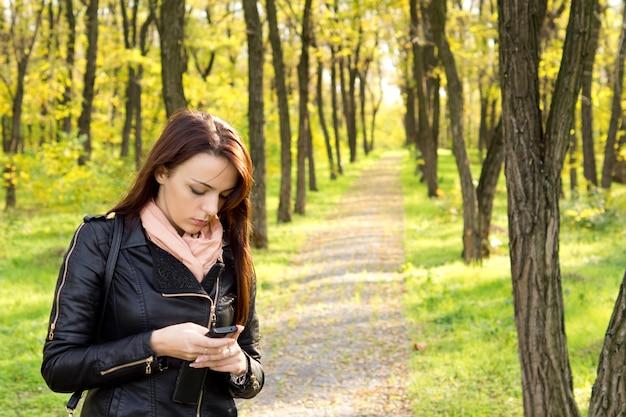 Ongerust gemaakte vrouw die op een voetpad door bos staat die een sms-bericht op haar mobiele telefoon leest