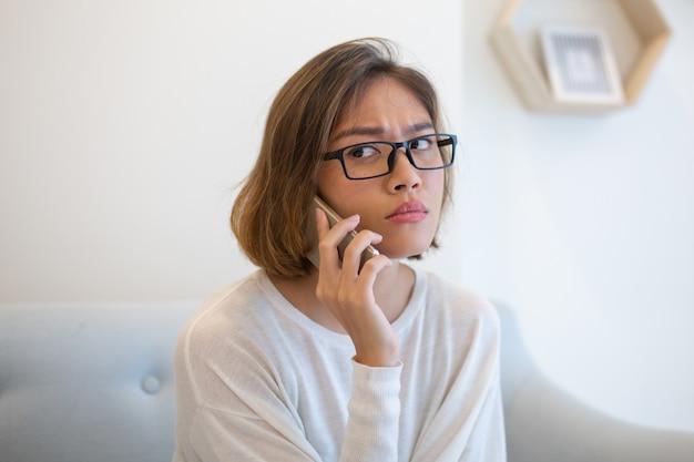 Ongerust gemaakte vrouw die smartphone op bank thuis uitnodigen