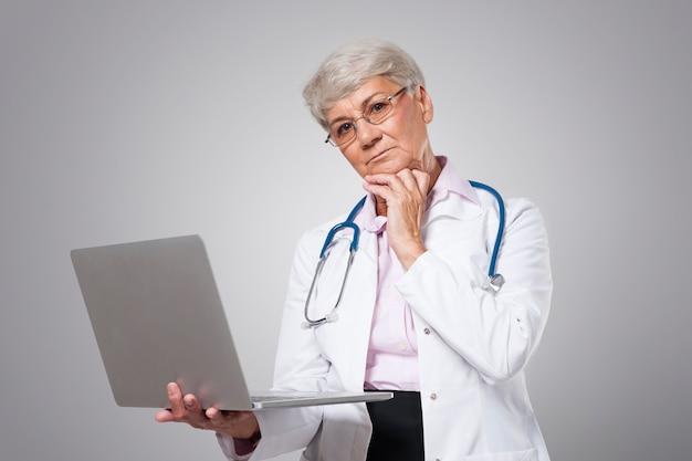 Ongerust gemaakte vrouwelijke hogere arts met laptop