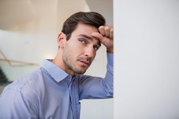Ongerust gemaakte zakenman met hand op hoofd dat op muur leunt