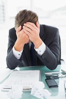 Ongerust gemaakte zakenman met hoofd in handen bij bureau