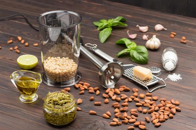 Ongeschilde pijnboompitten, pestosaus in pot en parmezaan op rasp