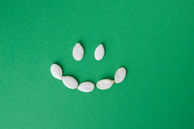Ongeschilde pompoenpitten zijn neergelegd in een smiley op een groene achtergrondkopieruimte