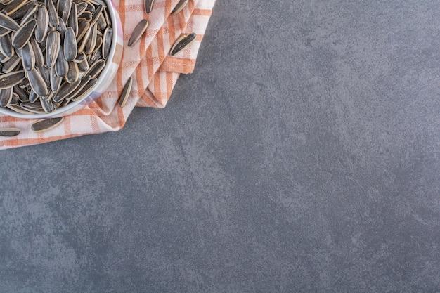 Ongeschilde zonnebloempitten in beker op handdoek, op het marmeren oppervlak